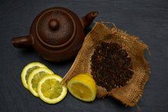 Theepot, half en plakken van rijpe citroen, droge theebladen op zwart s Stock Afbeelding