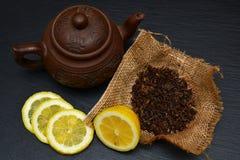Theepot, half en plakken van rijpe citroen, droge theebladen op zwart s Royalty-vrije Stock Foto