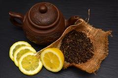 Theepot, half en plakken van rijpe citroen, droge theebladen op zwart s Stock Foto's