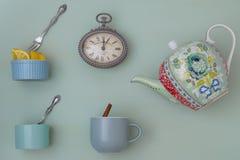 Theepot met koppen, en lepels en horloge stock afbeeldingen