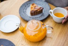 Theepot oranje thee en een pice van cake stock fotografie