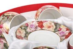 Theestel in een rode ronde doos met witte doek Schotels en theekoppen Stock Afbeelding