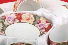 Theestel met bloemenpatroon in een doos met witte doek Schotels en theekoppen Stock Foto