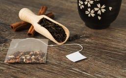 Theezakje op de achtergrond met een lepel van bladthee en kom voor thee Stock Foto