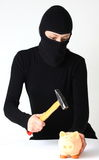 Theft breaking. A masked theft breaking a piggy bank with hammer isolated on white a background royalty free stock images