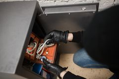 Thief stealing valuables from safe at crime scene. Theft, burglary and people concept - thief in mask stealing valuables from safe at crime scene staged photo Stock Photo