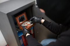Thief stealing valuables from safe at crime scene. Theft, burglary and people concept - thief in mask stealing valuables from safe at crime scene staged photo Stock Photography