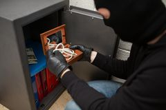 Thief stealing valuables from safe at crime scene. Theft, burglary and people concept - thief in mask stealing valuables from safe at crime scene Royalty Free Stock Image