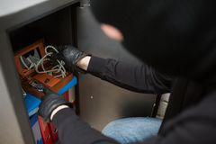 Thief stealing valuables from safe at crime scene. Theft, burglary and people concept - thief in mask stealing valuables from safe at crime scene Stock Image