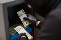 Thief stealing money from safe at crime scene. Theft, burglary and people concept - thief stealing money from safe at crime scene Stock Photography