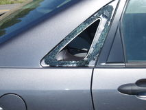 Theft from car. Car window broken by a thief to gain entry to its contents stock images