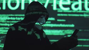 Theft of personal data on the network. robber in the mask and hood against the background of the running code. anonym. The hacker in the mask hacks the program stock video