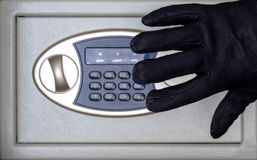 Theft of valuables or money from the safe. Hand in a black glove on the background of buttons of the code lock. Protection and. Theft of valuables or money from royalty free stock images