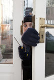 Theif breaking-in burglary security. Breaking and entering home or house, Burglar with screwdriver force open door. Thief attempting to breach security Stock Photos