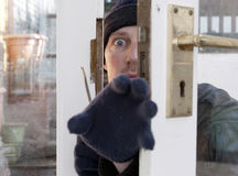 Theif breaking-in burglary security. Breaking and entering home or house, Burglar with screwdriver force open door. Thief attempting to breach security Royalty Free Stock Photos