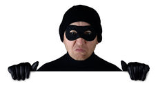 Theif. Thief peering over the top of isolated white copy space Stock Photo