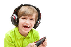 Thel boy plays with mobile and headphones Royalty Free Stock Image