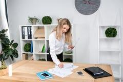 Thema bedrijfsvrouw op het werk Het mooie jonge Kaukasische vrouwen bedrijfsman werken die zich in het bureau dichtbij de lijst,  royalty-vrije stock afbeelding