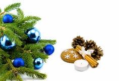 Thema des neuen Jahres: Weihnachtsbaum, blaue Bälle, Dekorationen, Kerze, Schneeflocken, Plätzchen, Kegel, Zimt lokalisiert Stockfotos