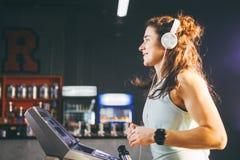 Thema ist Sport und Musik Eine schöne aufgeblähte Frau läuft in die Turnhalle auf einer Tretmühle Auf ihrem Kopf sind große weiße stockfotografie