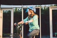 Thema om aan de fiets te werken Een jonge Kaukasische vrouw kwam op milieuvriendelijke vervoerfiets aan aan het bureau Meisje in  royalty-vrije stock fotografie
