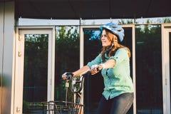 Thema om aan de fiets te werken Een jonge Kaukasische vrouw kwam op milieuvriendelijke vervoerfiets aan aan het bureau Meisje in  stock foto's