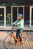 Thema om aan de fiets te werken Een jonge Kaukasische vrouw kwam op milieuvriendelijke vervoerfiets aan aan het bureau Meisje in  stock afbeeldingen