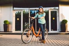 Thema om aan de fiets te werken Een jonge Kaukasische vrouw kwam op milieuvriendelijke vervoerfiets aan aan het bureau Meisje in  stock fotografie