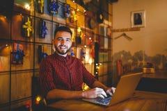 Thema opleiding en computers Een jonge mens met een baard en in een overhemd gebruikt laptop, drukt op het toetsenbord in een kof stock foto