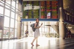 Thema Reise und tranosport Schöne junge kaukasische Frau im Kleid und in Rucksack, die inneres Bahnstation oder Anschluss looki s stockfotografie