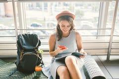 Thema van toerisme en reis van jonge student Het mooie jonge Kaukasische meisje in kleding en hoed zit binnen op de deken van de  royalty-vrije stock afbeelding
