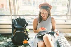 Thema van toerisme en reis van jonge student Het mooie jonge Kaukasische meisje in kleding en hoed zit binnen op de deken van de  stock fotografie