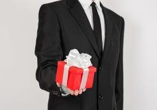 Themafeiertage und -geschenke: ein Mann in einem schwarzen Anzug hält exklusives Geschenk eingewickelt im roten Kasten mit weißem Stockbild