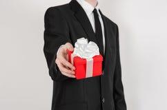 Themafeiertage und -geschenke: ein Mann in einem schwarzen Anzug hält exklusives Geschenk eingewickelt im roten Kasten mit weißem Stockfoto
