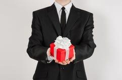 Themafeiertage und -geschenke: ein Mann in einem schwarzen Anzug hält exklusives Geschenk eingewickelt im roten Kasten mit weißem Stockfotografie