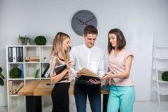 Themageschäft, -teamwork und -partnerschaften Eine Gruppe junge Leute, drei Leute, Stand in einem Büro nahe der Tabelle herein stockfotos