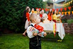 Themakinder Feiertag, Geburtstag Ein kleiner Junge, der im Hof des Hauses mit dem blonden Haar, gekleidet in Klage und in rotem S Lizenzfreie Stockfotografie