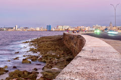 TheMalecon seawall in Havana at sunset with a view of the city skyline. The famous Malecon seawall in Havana at sunset with a view of the city skyline Stock Photos