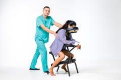 Themamassage en bureau Mannelijke therapeut met het blauwe kostuum doen terug en halsmassage voor jonge vrouwenarbeider, bedrijfs stock foto's
