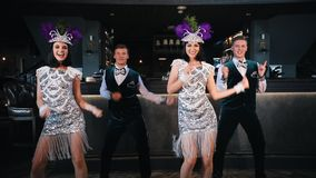 Themapartij - Jonge glimlachende mensen in het glinsteren het retro kleren dansen stock footage