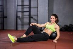Themasport en gezondheid Een sterke spier Kaukasische vrouw in de gymnastiek ligt met haar terug op een opgevulde zwarte het kned stock foto