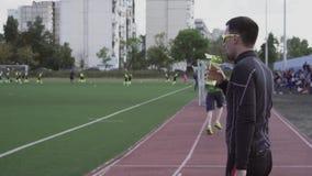 Themasport en gezondheid Het jonge Kaukasische mannelijke drinkwater van de atletenagent van een sportenfles bij een stadsstadion stock footage