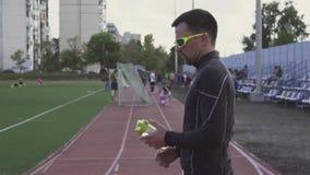 Themasport en gezondheid Het jonge Kaukasische mannelijke drinkwater van de atletenagent van een sportenfles bij een stadsstadion stock videobeelden