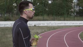 Themasport en gezondheid Het jonge Kaukasische mannelijke drinkwater van de atletenagent van een sportenfles bij een stadsstadion stock video