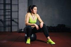 Themasport und -gesundheit Starke muskulöse kaukasische Frau in der Turnhalle, die auf einem schwarzen schweren aufgefüllten fitb stockfoto