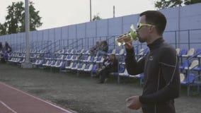 Themasport und -gesundheit Trinkwasser des jungen kaukasischen m?nnlichen Athletenl?ufers von einer Sportflasche an einem Stadtst stock footage
