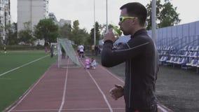 Themasport und -gesundheit Trinkwasser des jungen kaukasischen m?nnlichen Athletenl?ufers von einer Sportflasche an einem Stadtst stock video