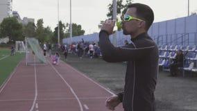 Themasport und -gesundheit Trinkwasser des jungen kaukasischen m?nnlichen Athletenl?ufers von einer Sportflasche an einem Stadtst stock video footage