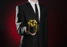 Themavakantie en giften: een mens in een zwart kostuum houdt exclusieve die gift in een zwarte doos met gouden lint en boog op do Stock Afbeeldingen