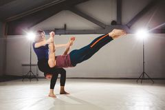 The theme of Acroyoga and Yoga Poses. Acroyogis practicing. with the studio Backlight. The woman Base keeps the man Flyer in the h. The theme of Acroyoga and Royalty Free Stock Images